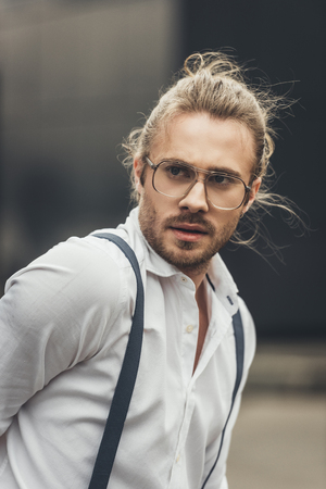 handsome stylish young man in spectacles and suspenders looking away