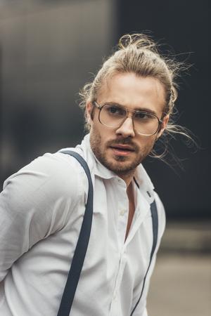 knappe stijlvolle jonge man in bril en ophangers wegkijken