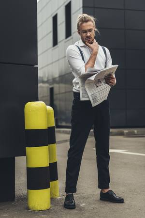 young man in eyeglasses reading newspaper while standing with hand on chin Stockfoto