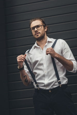 stylish man in spectacles adjusting suspenders and looking away
