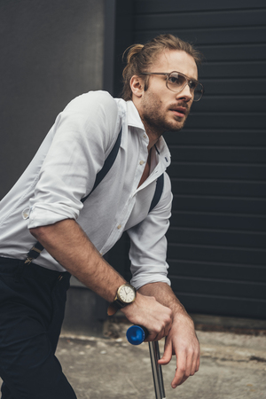 bearded young man in eyeglasses standing on scooter and looking away