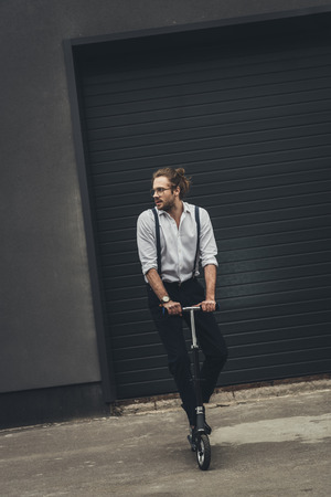 young man in eyeglasses and suspenders standing on scooter and looking away Stockfoto