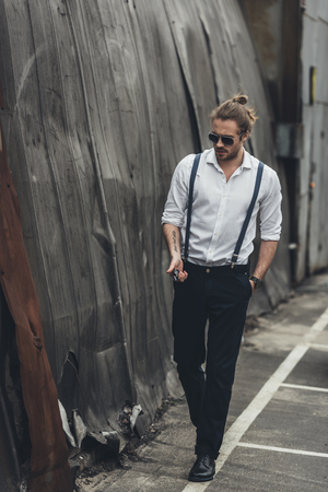bearded stylish man in formal wear and sunglasses holding lighter and walking with hand in pocket