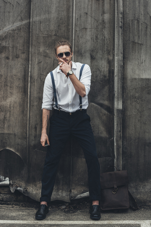 confident young man smoking cigarette and looking at camera Stok Fotoğraf