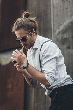 handsome stylish bearded man in sunglasses and suspenders lighting cigarette with lighter