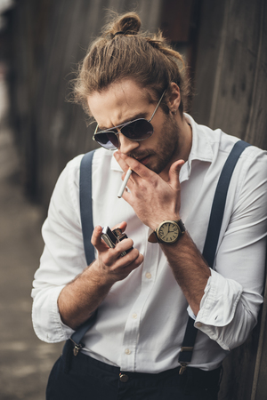 bearded handsome man in sunglasses lighting cigarette with lighter