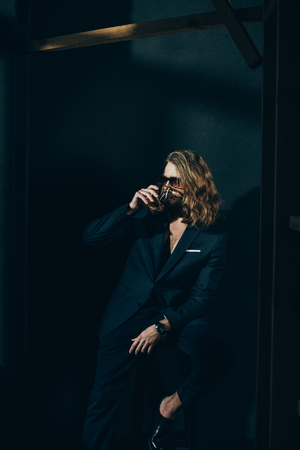 stylish long haired man in suit drinking whiskey on black Stock Photo