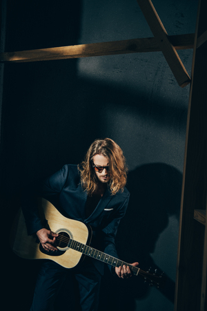 stylish man in suit and sunglasses playing guitar on black