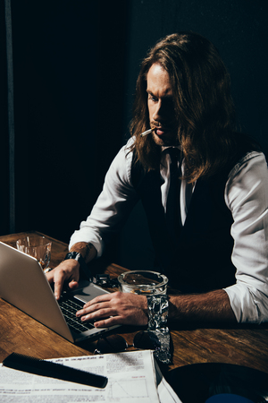 long haired man in formal wear smoking cigarette and typing on laptop