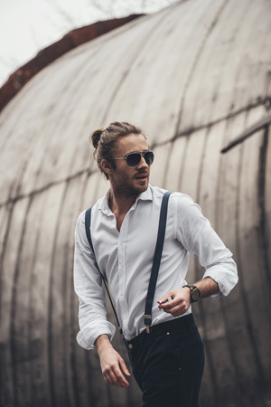 stylish young man in sunglasses holding cigarette and looking away