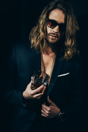 bearded long haired man in sunglasses and stylish suit holding glass of whiskey on black