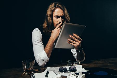 young stylish man using digital tablet while smoking cigar on black