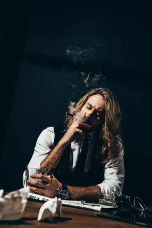 stylish young man drinking alcohol and smoking cigar while sitting at table Imagens