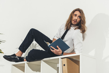 young long haired businessman lying on bookshelf and reading book in office