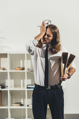 young businessman holding eyeglasses and folders while standing in office Stock Photo