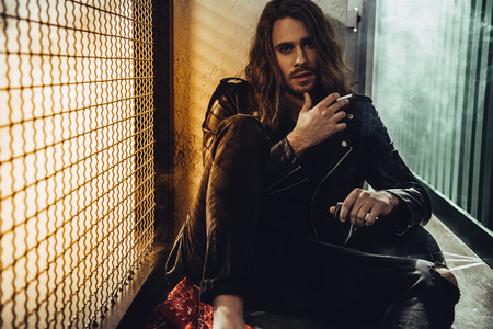 bearded long haired man in leather jacket smoking cigarette and looking at camera