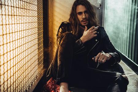 bebaarde langharige man in lederen jas roken van sigaretten en kijken naar de camera