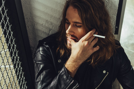 bearded long haired man in leather jacket smoking cigarette and looking away Stok Fotoğraf