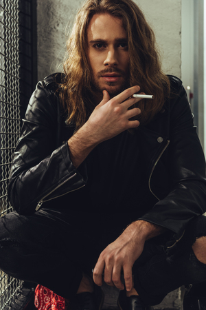 stylish bearded man in leather jacket smoking cigarette and looking at camera