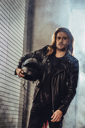 long haired bearded man in leather jacket holding helmet and looking at camera