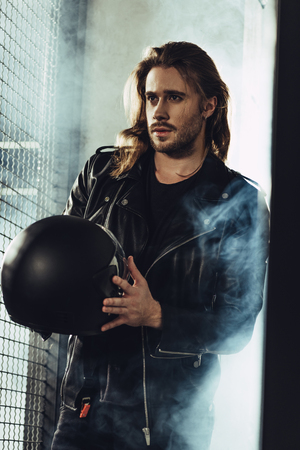 bearded stylish man in leather jacket holding helmet and looking away