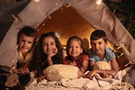 children resting in handmade tent together at home Stock Photo