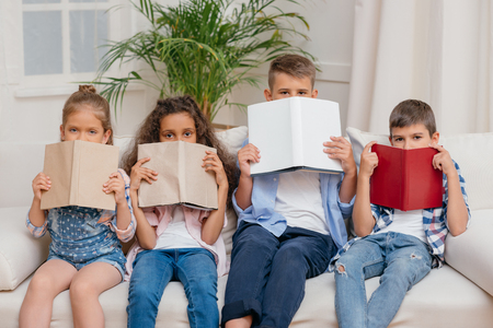 children covering faces with books while sitting on sofa Stock fotó