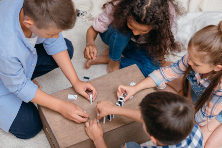 multicultural group of kids playing domino on wooden box Standard-Bild