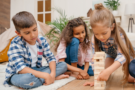 children playing blocks wood game together at home