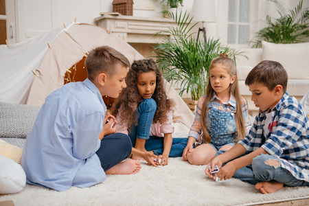children playing domino game together at home Banco de Imagens