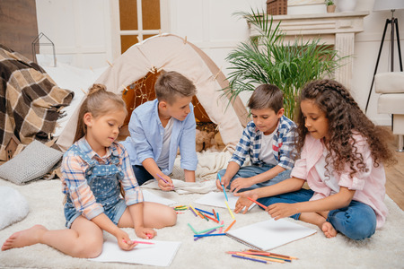 kids drawing pictures with pencils at home