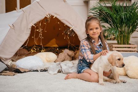 smiling caucasian girl hugging labrador puppy at home
