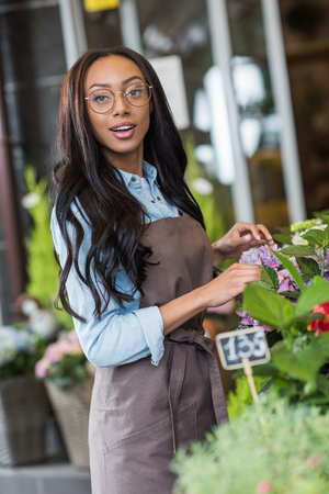 african american florist in apron and eyeglasses working in flower shop and smiling at camera
