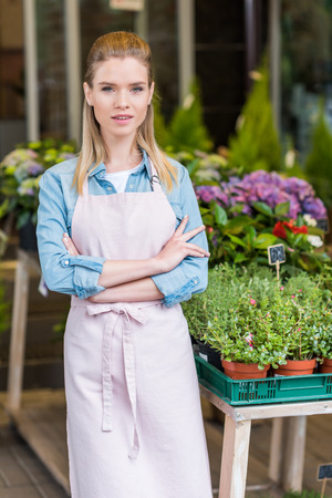 young florist in apron standing with crossed arms and looking at camera Banco de Imagens