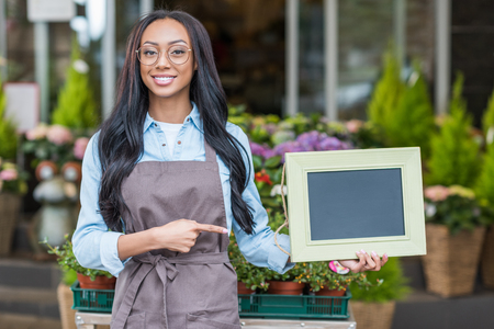 african american florist in eyeglasses holding blank sign and pointing at copy space