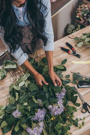 young african american woman arranging flowers and green leaves in flower shop