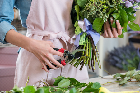 young florist in apron holding bouquet and cutting green stems with secateurs