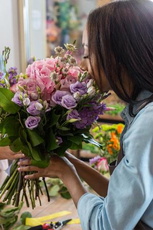 african american woman smelling beautiful flowers in flower shop