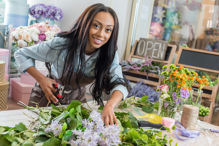 african american woman in apron holding secateurs while cutting flowers and smiling at camera in flower shop