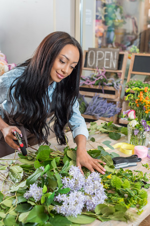smiling african american florist holding secateurs and working with flowers