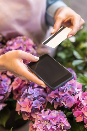 person holding smartphone and credit card while standing in flower shop