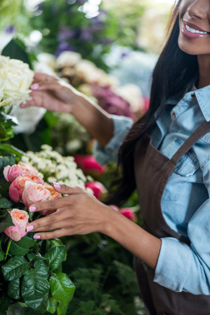smiling african american florist working with flowers