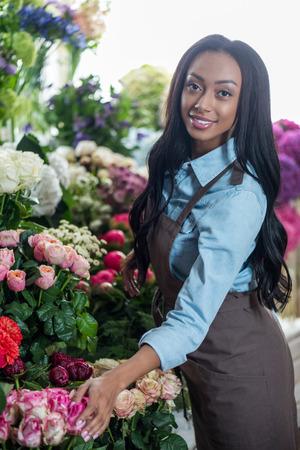 젊은 아프리카 계 미국인 꽃집 꽃과 함께 포즈와 카메라에 웃 고 플로리스트