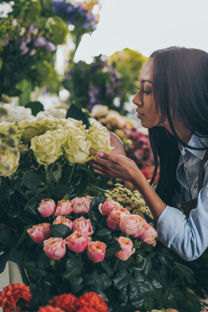 african american woman smelling beautiful roses in flower shop