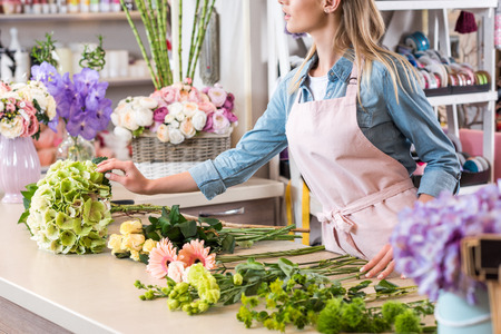 young blonde florist in apron arranging beautiful flowers in flower shop