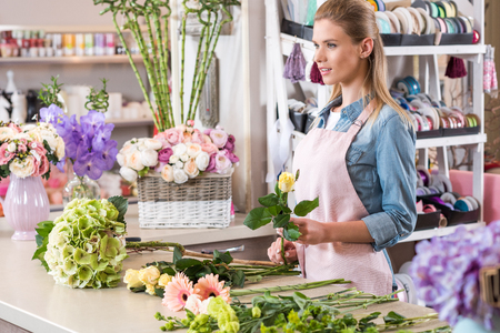 young blonde florist in apron working with fresh flowers and looking away in flower shop