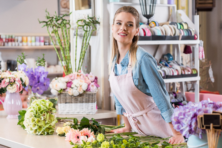 smiling blonde woman in apron working with fresh flowers and looking away in flower shop
