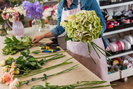 young florist in apron working with flowers and arranging bouquet Banco de Imagens
