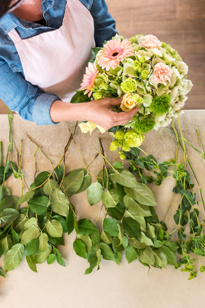 young woman in apron working with bouquet of beautiful fresh flowers