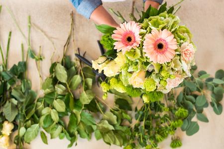 florist arranging beautiful fresh flowers in bouquet